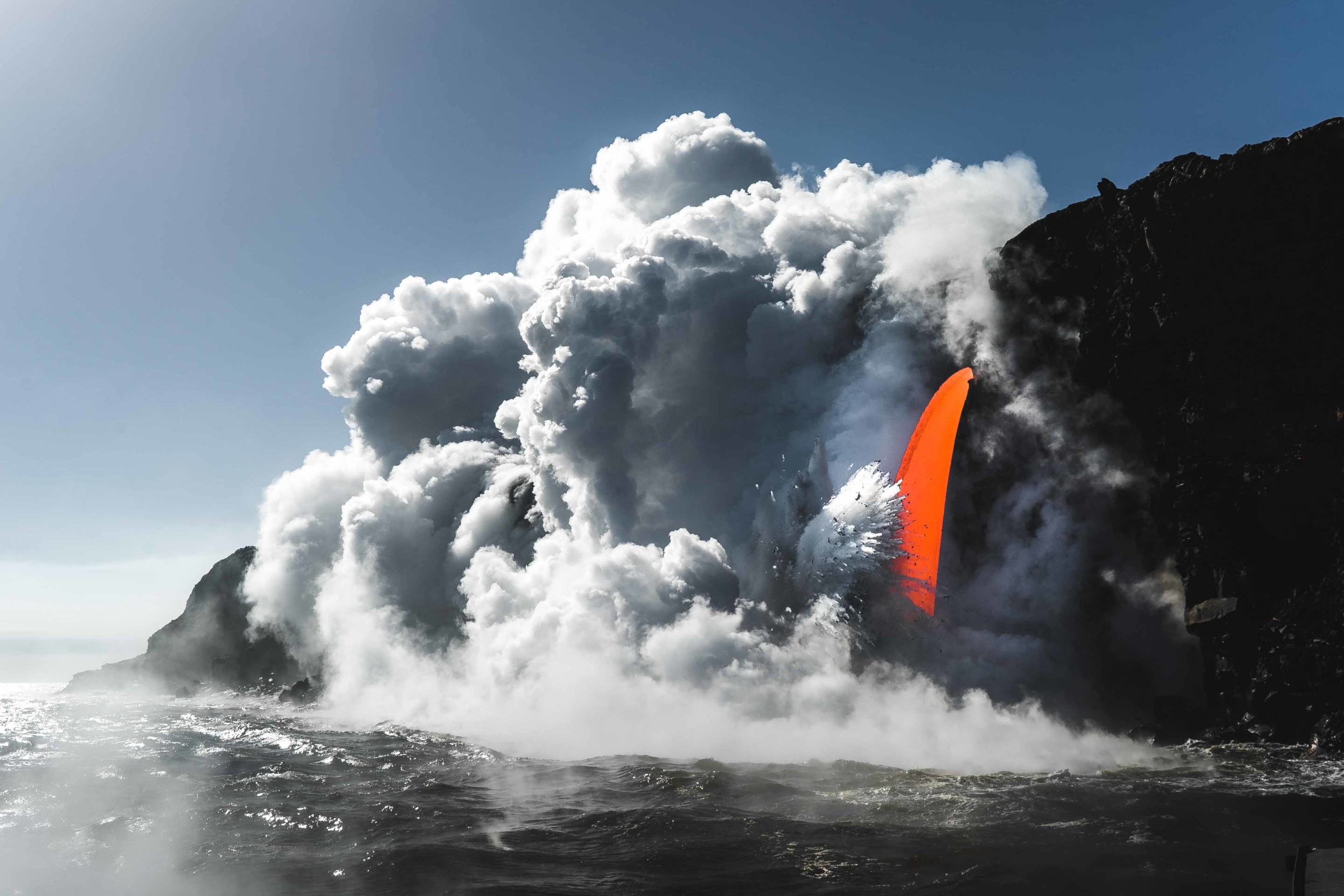 A fire hose lava spout in Hawaii Volcanoes National Park viewed from a boat
