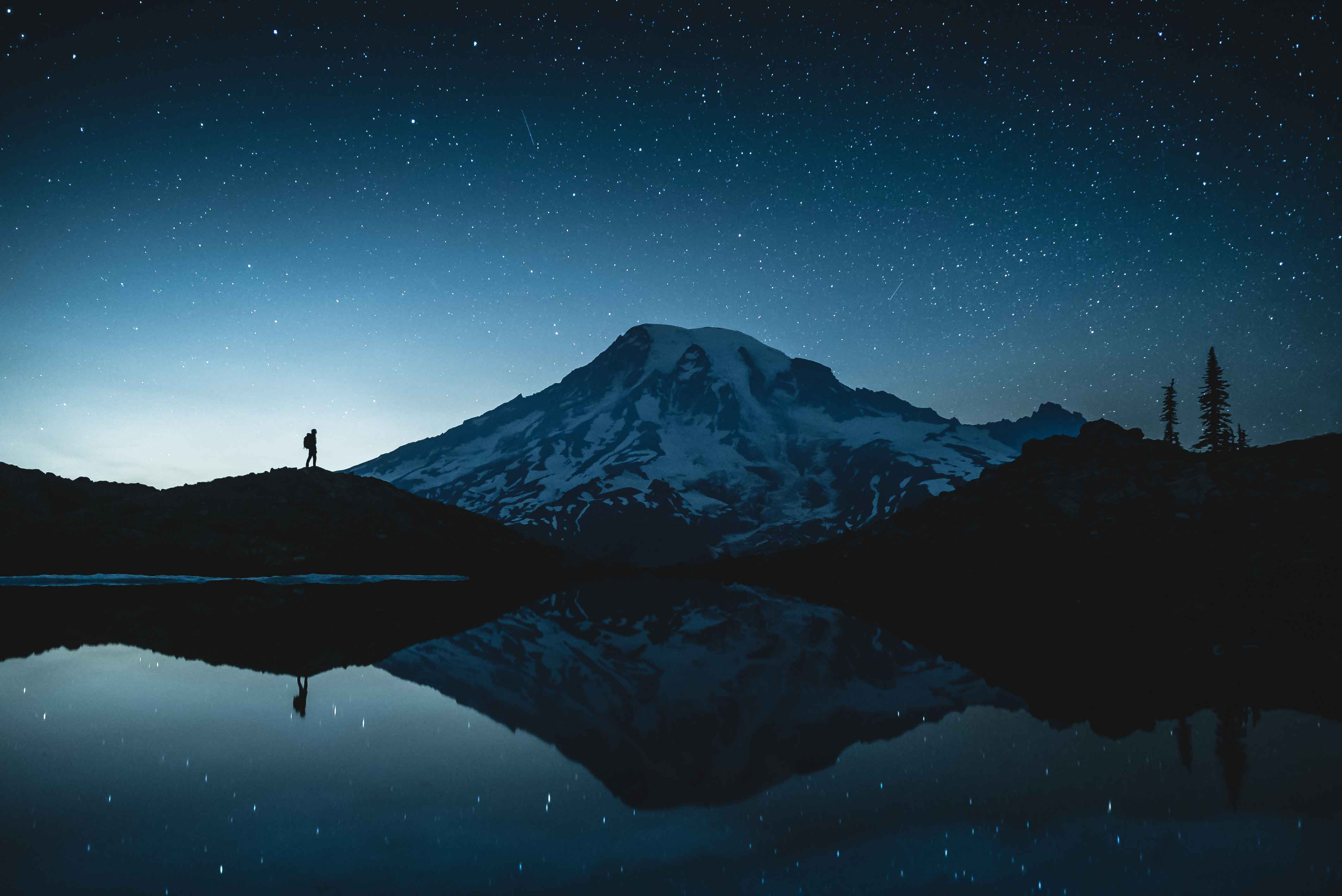 Star photography of a person standing reflected in a small glacier tarn on Mount Rainier, Washington below the stars