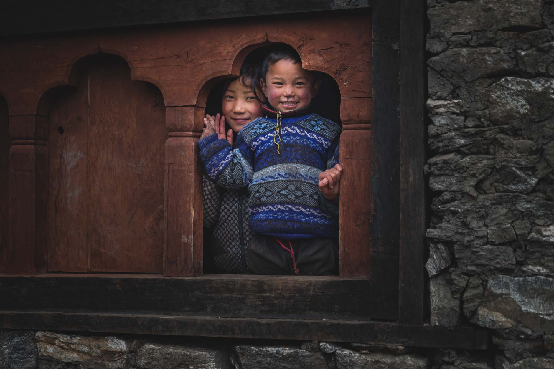 Photography of two young Bhutanese children in a window in Laya, Bhutan