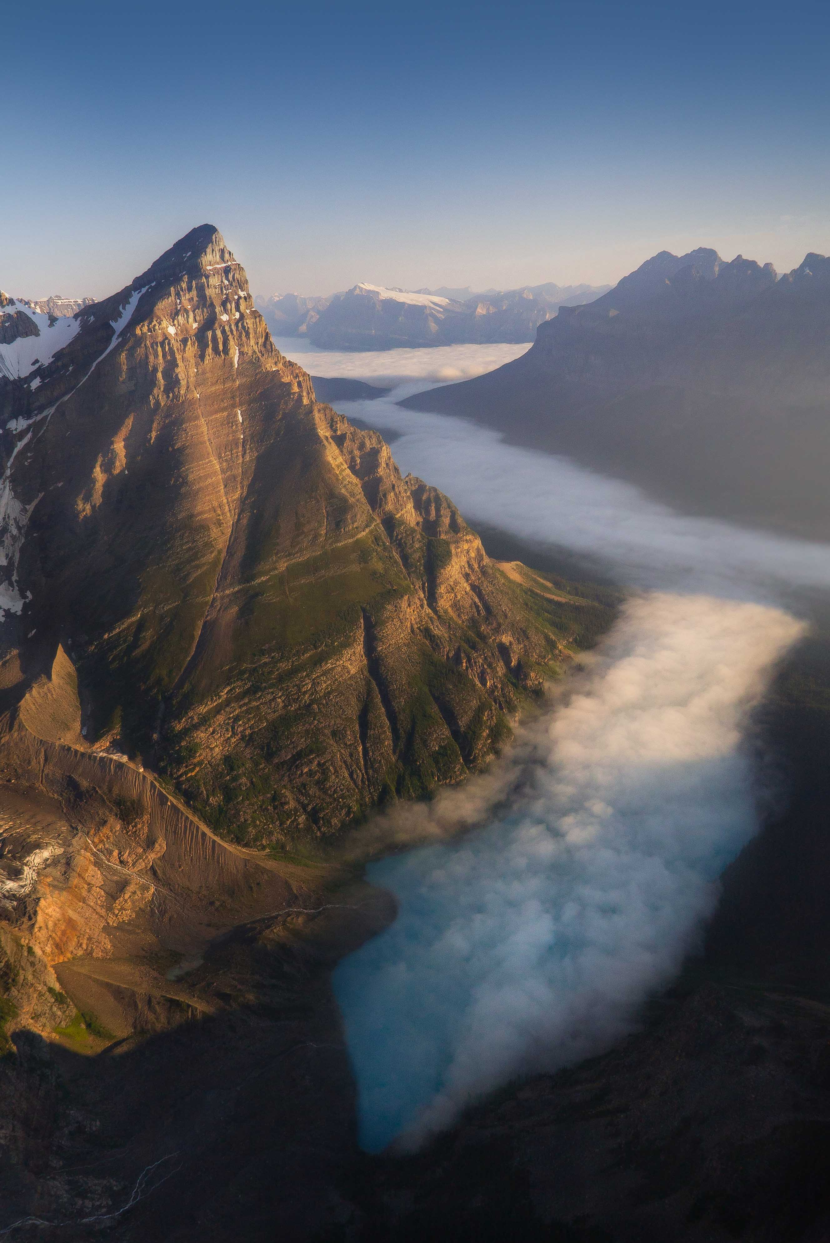 Aerial photography of mount chephren in Banff National Park during sunrise above the fog Photo by Andrew Studer