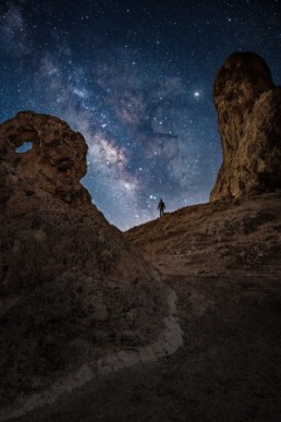 Night photography of a person standing below the milkyway at the Trona Pinnacles in California