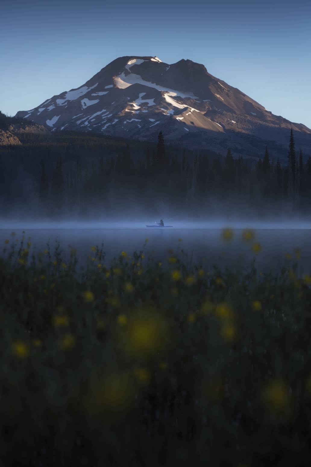 A person in a yellow kayak paddles during sunrise below a mountain near Bend Oregon at Sparks Lake