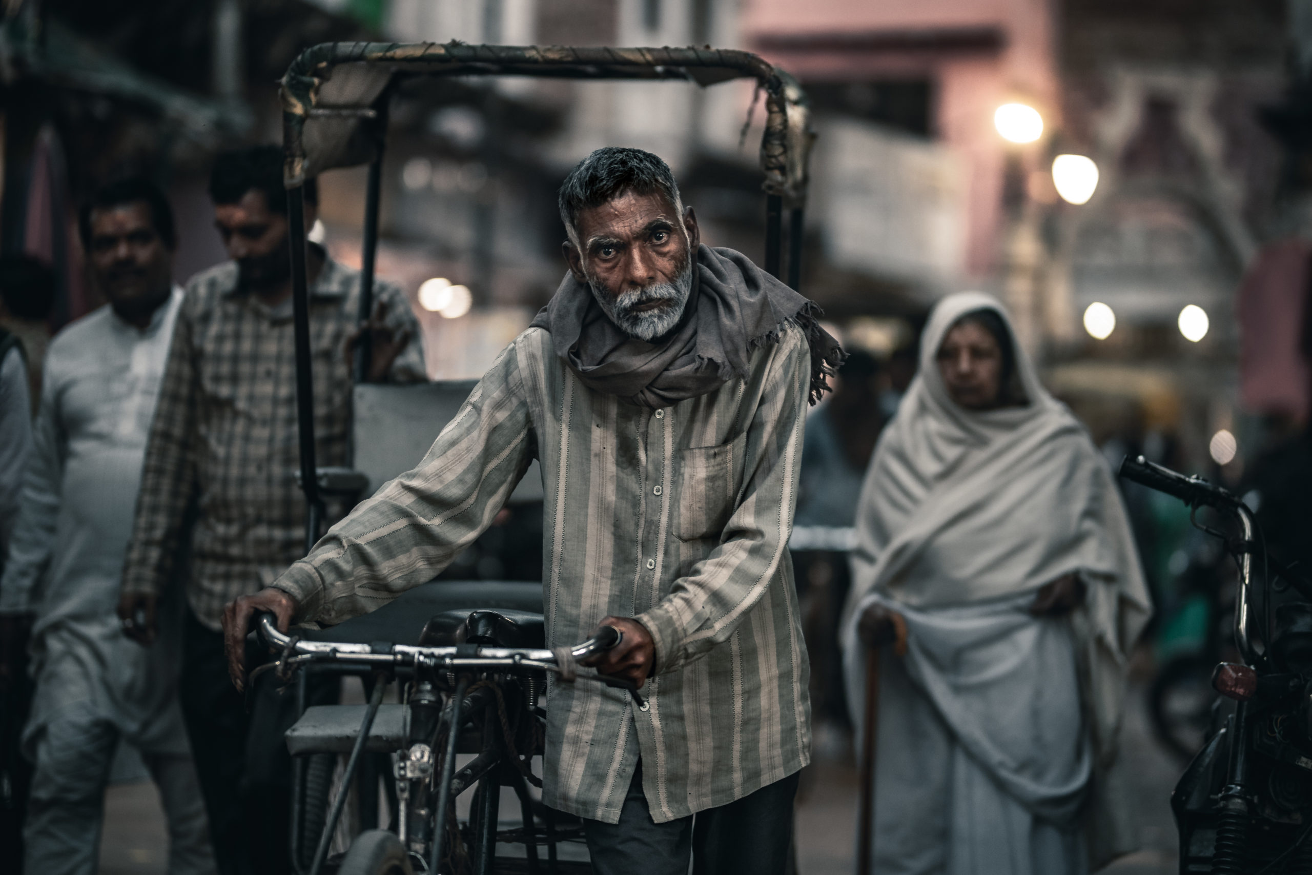 Portrait street photography of a rickshaw driver walking in the streets of Mathura, India
