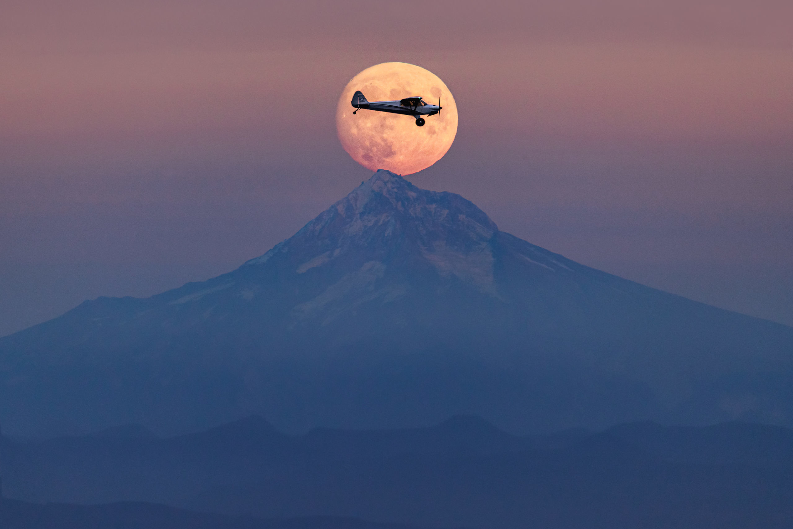 Aviation photography of a Carbon Cub airplane inside the rising full moon at sunset over Mount Hood, Oregon