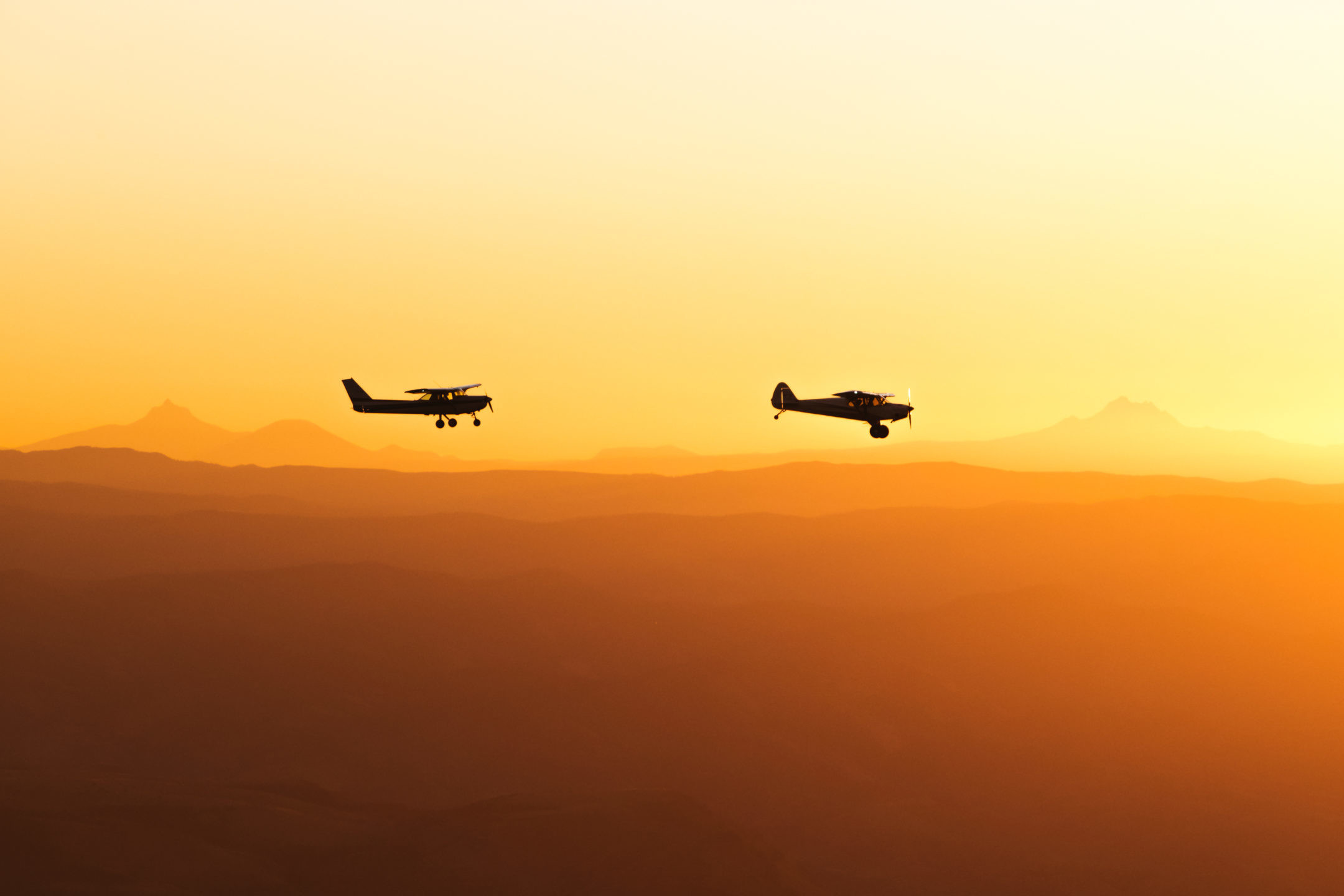 Aviation Photography of two airplanes flying over mountains in Oregon during Sunset