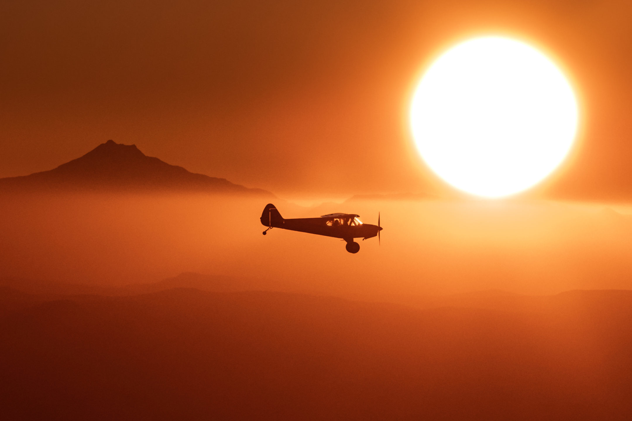 Aviation Landscape photography of a Carbon Cub airplane flying over Oregon during sunset.